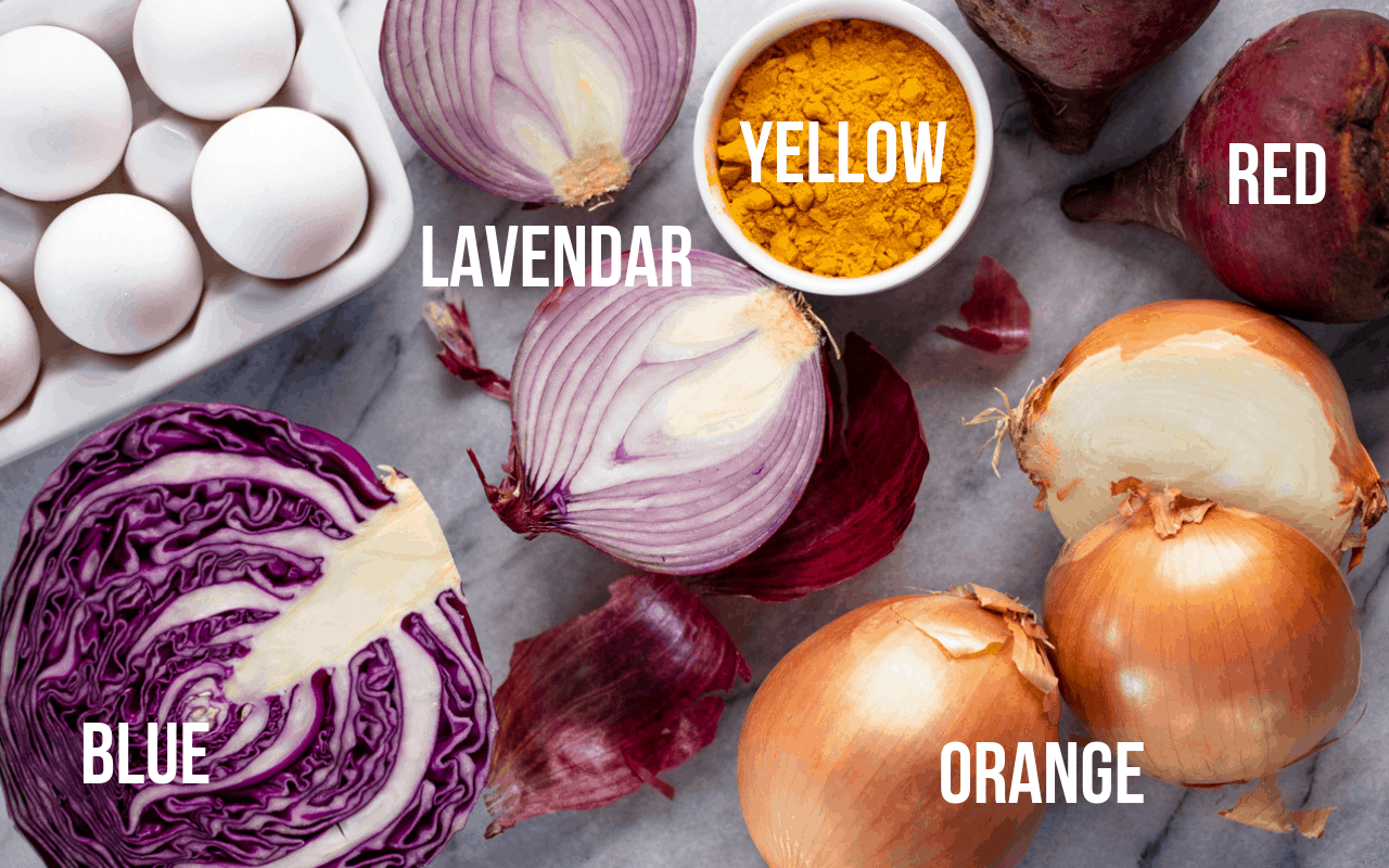 Vista de pájaro de un repollo morado, cebollas moradas, un tazón de cúrcuma, remolacha y cebollas amarillas, todos etiquetados con el color que teñirán el huevo.